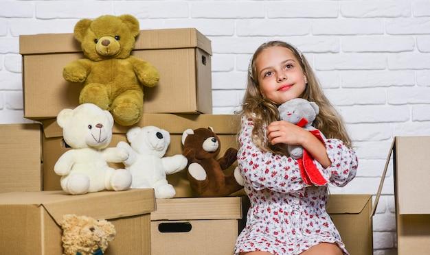 Meisje klein kind en dozen. bereid je voor om te verhuizen. huurhuis. onroerend goed. dromen over eigen kamer. verhuisconcept. kind gaat verhuizen. het bezorgen van uw aankoop. beweegroutine. dingen verpakken.