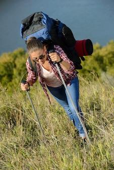 Meisje klimt de berg op met een grote rugzak.