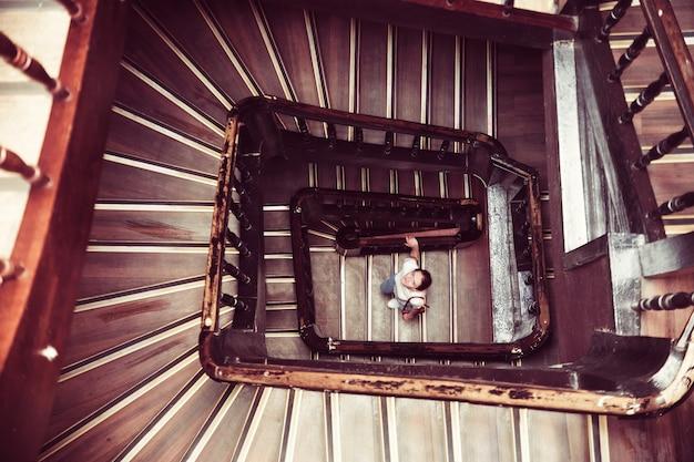 Meisje klimt een wenteltrap. recht boven.