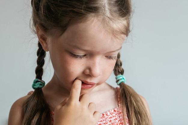 Meisje knaagt aan nagels, houdt haar vingers in haar mond, slechte gewoonten van kinderen, concept.