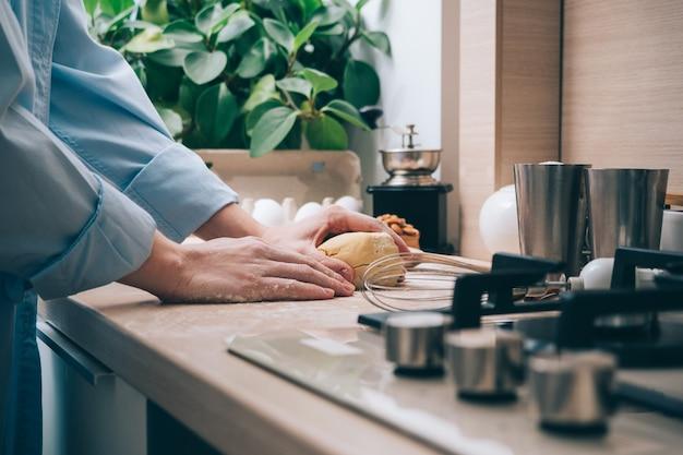 Meisje kneden van deeg in de keuken, close-up. een vrouw thuis bereidt deeg voor heerlijke gebakjes of koekjes. culinaire achtergrond.
