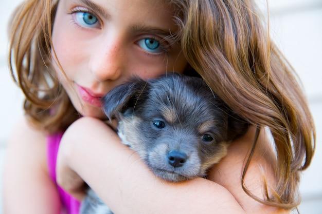 Meisje knuffel een kleine puppy hond grijze harige chihuahua