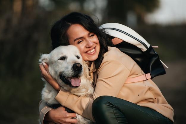 Meisje knuffelen een golden retriever-hond in het bos Premium Foto
