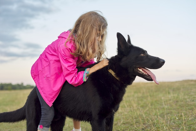 Meisje knuffelen grote zwarte hond herder, kind en huisdier wandelen in de natuur