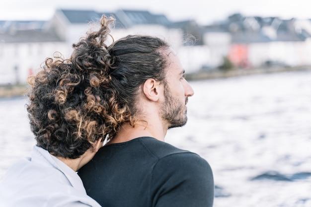 Meisje knuffelen haar partner terug met de zee onscherp