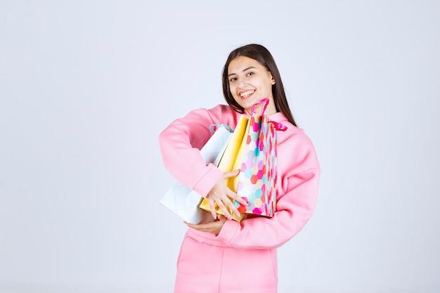 Meisje knuffelen kleurrijke boodschappentassen en een positief gevoel.