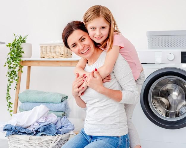 Meisje knuffelen met moeder tijdens het wassen van kleren in de wasmachine thuis