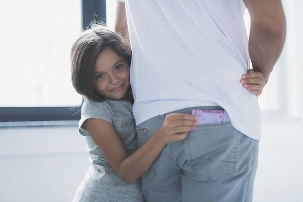 Meisje knuffels vader steelt geld uit jeans zak