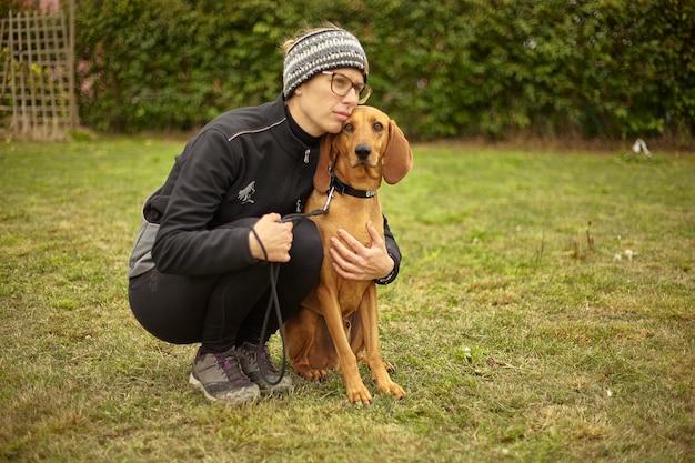 Meisje knuffelt haar hond terwijl ze in het park zijn