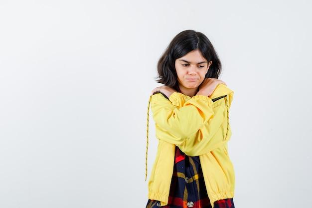 Meisje knuffelt zichzelf in een geruit overhemd, jasje en ziet er schattig uit