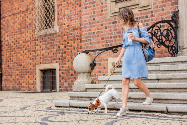 Meisje komt de trap af met een hond en een kopje koffie