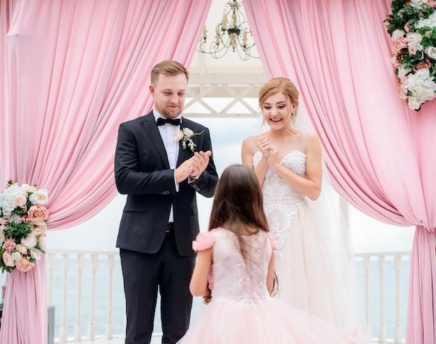 Meisje komt naar de bruid en bruidegom met trouwringen tijdens de ceremonie