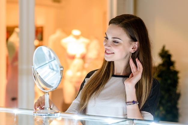 Meisje koopt oorbellen in het winkelcentrum.