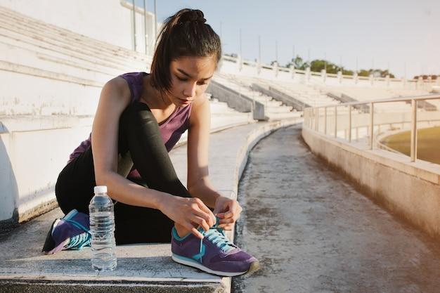 Meisje koppelverkoop haar sneakers naast een fles water