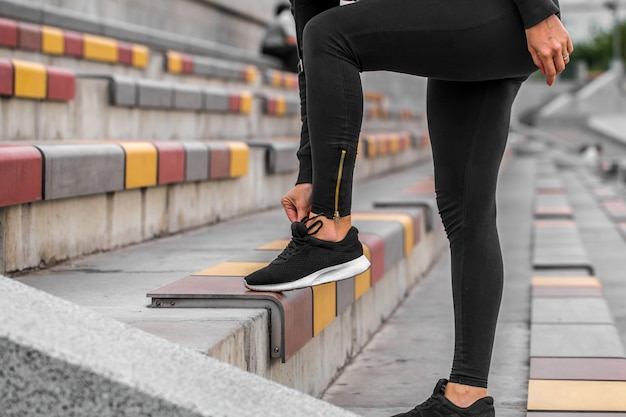 Meisje koppelverkoop schoenveters op sneakers