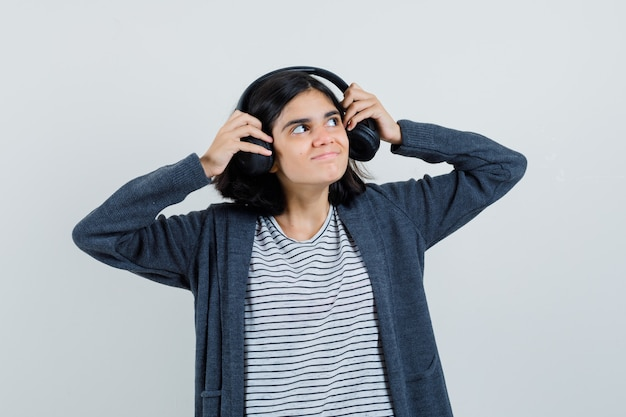 Meisje koptelefoon in t-shirt, jasje opstijgen en nieuwsgierig kijken