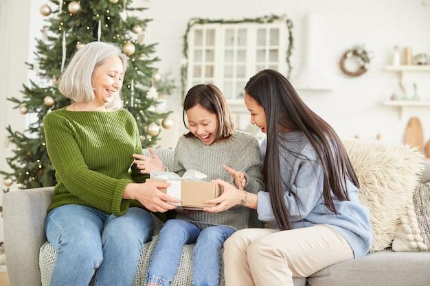 Meisje krijgt kerstcadeau van haar moeder en zus zittend op de bank thuis