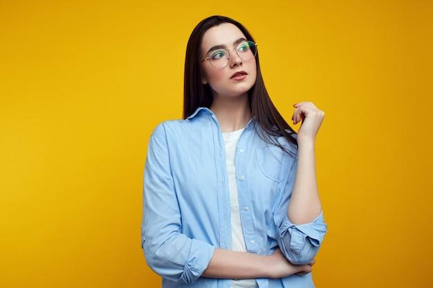 Meisje kruist arm over middel, kijkt naar links, draagt blauw shirt over gele muur