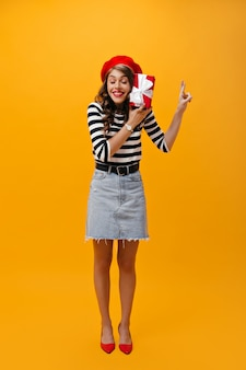 Meisje kruist vingers en houdt geschenkdoos op oranje achtergrond. koele vrouw in baret, denim rok, gestreepte shirt en rode hakken poseren.