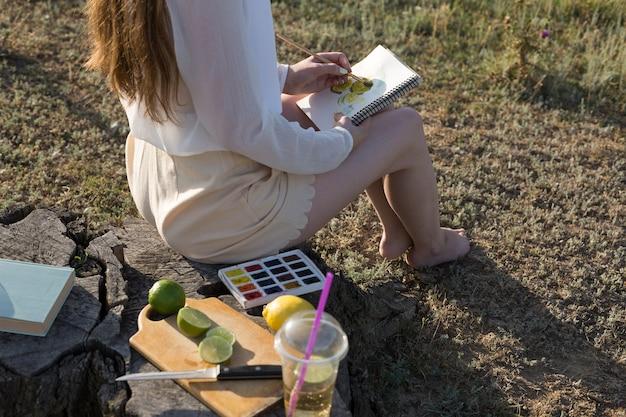 Meisje kunstenaar schildert een foto met aquarellen in de natuur.