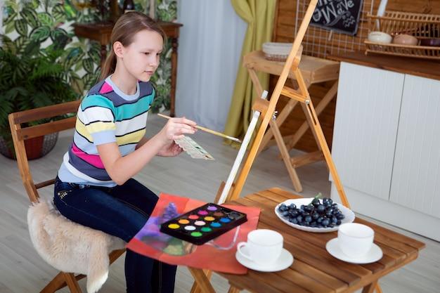 Meisje kunstenaar schildert een prachtige foto op canvas met olieverf