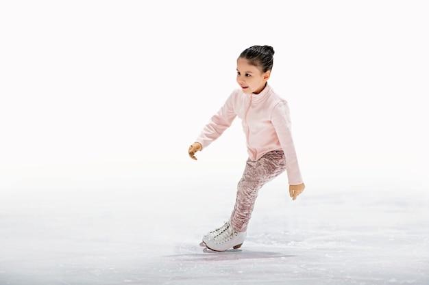 Meisje kunstschaatsster in een lichtroze trainingspak