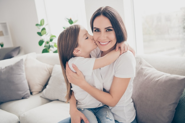 Meisje kus knuffelen moeder in kamer appartement binnenshuis