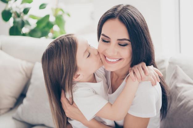 Meisje kussen wang jonge mama knuffelen haar in huis huis