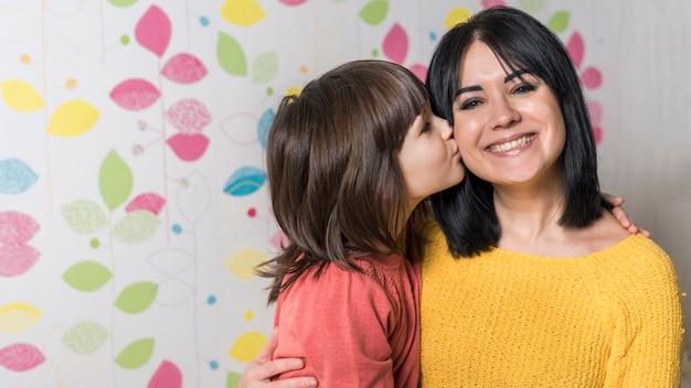 Meisje kussende moeder op wang
