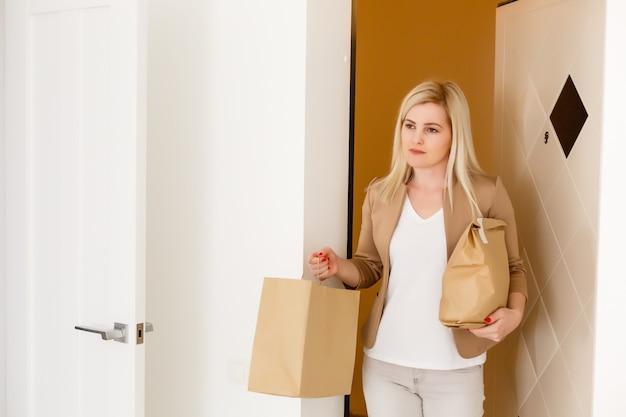 Meisje kwam thuis met een pakket eten. jonge vrouw mee naar huis genomen van supermarkt aankoop van producten. concept van een gezond dieet. huisvrouw met producten op de achtergrond van de deur van het huis
