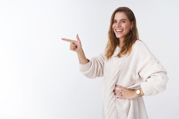 Meisje lachen glimlachend gelukkig staand profiel wijzende wijsvingers kant draaien camera giechelen grijnzend vreugdevol tonen geweldige promo advertentie, blij met je delen, witte achtergrond