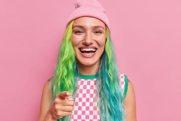Meisje lacht breed wijst naar jou vraagt om lid te worden van haar team heeft felgekleurd haar piercing in neus draagt hoed geruit hemd staat op roze