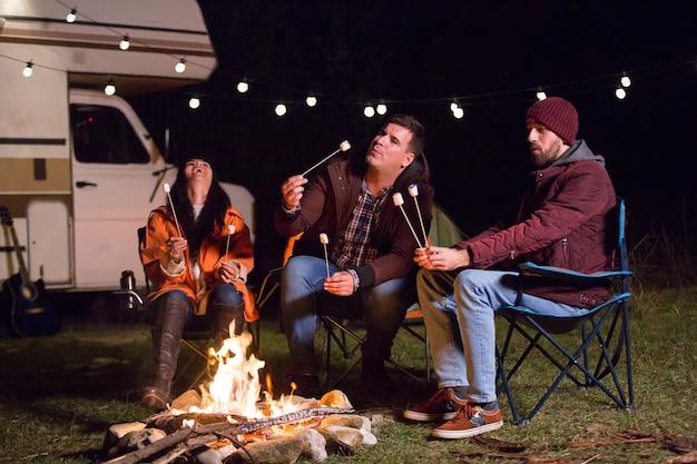 Meisje lacht en houdt hete marshmallow vast terwijl haar vrienden marshmallows roosteren. retro camper. kamperen in de bergen.