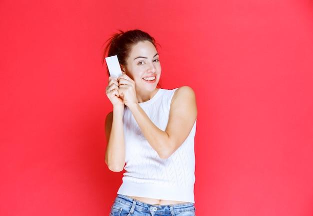 Meisje lacht en presenteert haar visitekaartje.