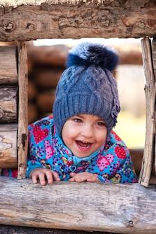 Meisje lacht en speelt in een houten huis