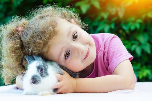 Meisje lacht, knuffelen baby konijn.