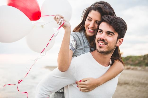 Meisje lacht met ballonnen, terwijl haar vriendje haar draagt op haar rug