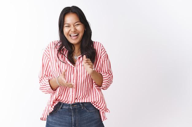 Meisje lacht om hilarische grap die applaudisseert en giechelt van plezier en vreugde. portret van een zorgeloze, aantrekkelijke jonge vrouw in een gestreepte blouse die grinnikt en in de handen klapt tijdens een stand-up comedyshow