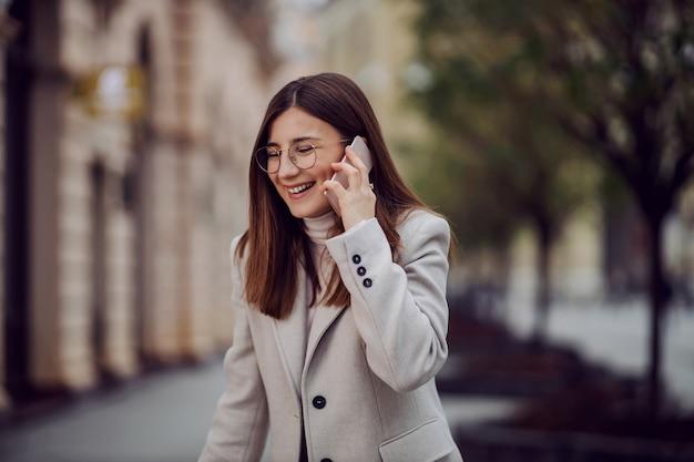 Meisje lacht op straat en praat aan de telefoon. duizendjarige generatie.