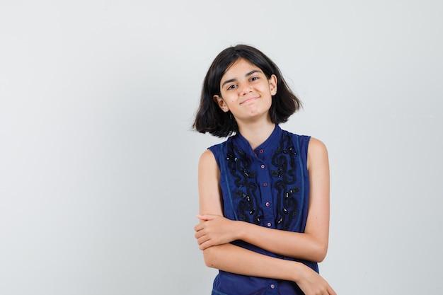 Meisje lacht terwijl het kijken naar camera in blauwe blouse