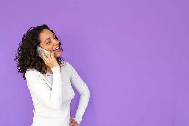 Meisje lacht tijdens het praten aan de telefoon. paarse achtergrond en kopie ruimte. wit casual overhemd. gekruld haar.