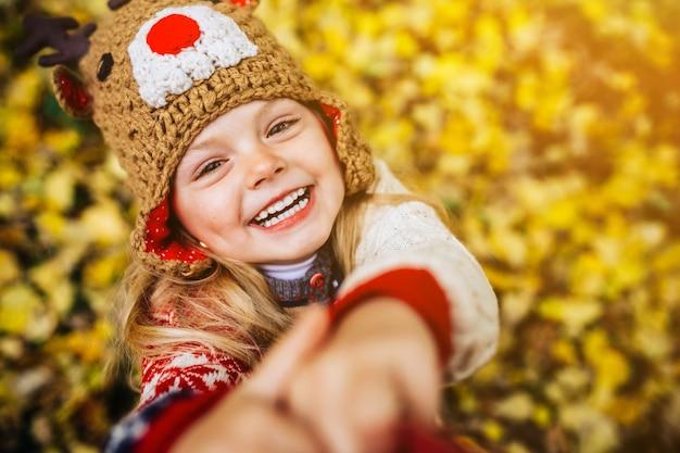 Meisje lacht vooraan op een achtergrond van gele bladeren