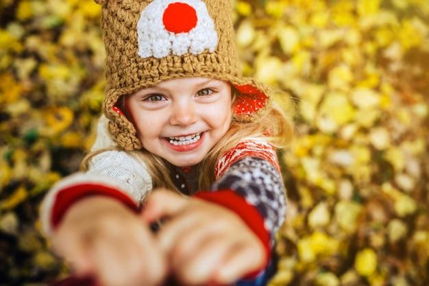 Meisje lacht vooraan op een achtergrond van gele bladeren Gratis Foto