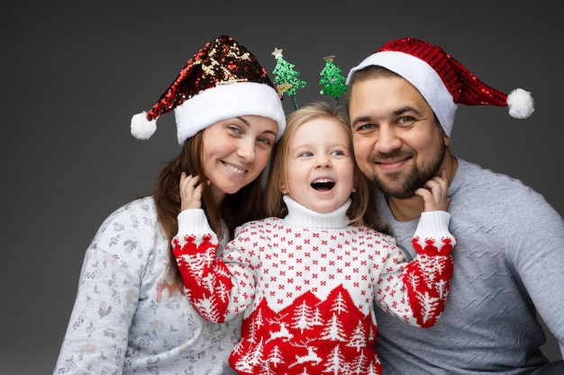 Meisje lacht vreugdevol terwijl ze een baard van haar vader en haar moeder haar krabt, terwijl de ouders ervan genieten.