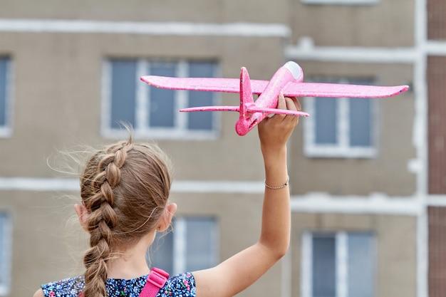 Meisje lanceert een roze speelgoedvliegtuig in de lucht tegen de achtergrond van een gebouw met meerdere verdiepingen