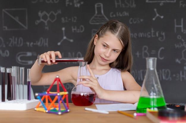Meisje leert meer over scheikunde in de klas