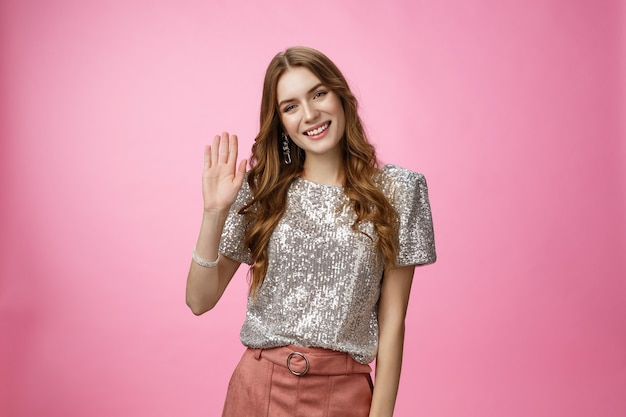 Meisje leert mensen kennen feest steek hand op zwaaiende palm glimlachend zeg hallo toon hallo gebaar groet vooravond...