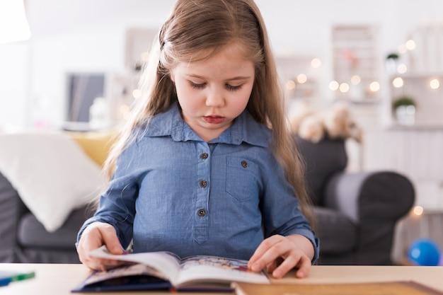 Meisje leesboek in de woonkamer