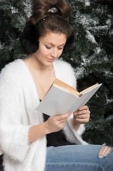 Meisje leest boek op de bank