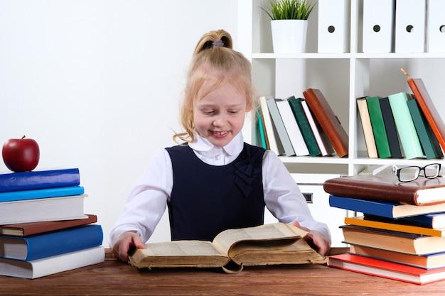 Meisje leest boeken aan de tafel